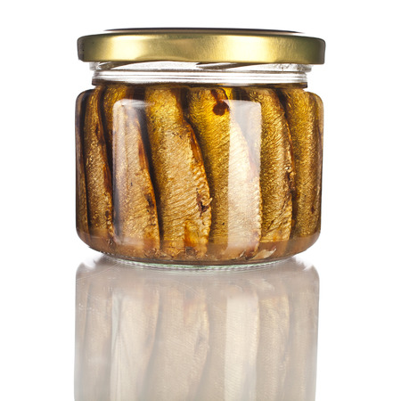conserved: Sardines fishes with oil conserved in glass jar close up isolated on the white background Stock Photo
