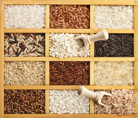 typesetter: Assortment of rice in wooden box with scoop surface top view