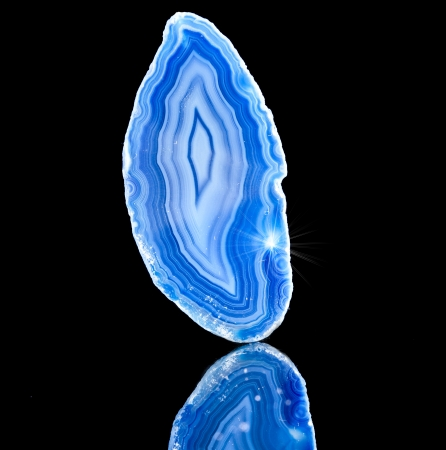 Thin slice of blue agate crystal with reflection on black surface  photo