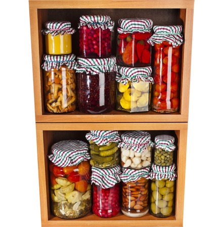 Variety glass bottles with preserved food in wooden cabinet Isolated on white  photo