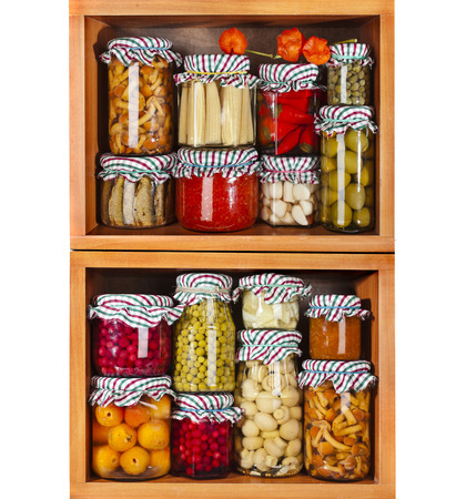 many glass bottles with preserved food in wooden cabinet Isolated on white background photo