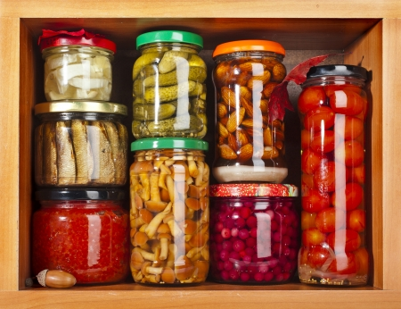 many glass bottles stack with preserved food in wooden cabinet photo