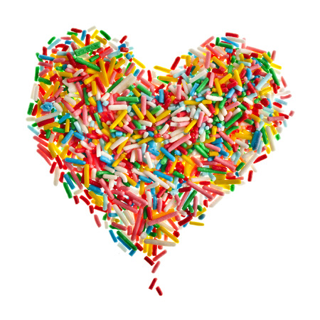 Colorful candy sprinkles heart shape isolated on white background Imagens