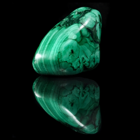 Polished malachite stone close up with reflection on black surface background photo