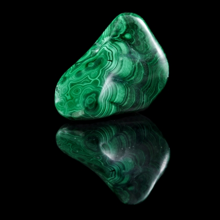 malachite: Polished malachite stone close up with reflection on black surface background