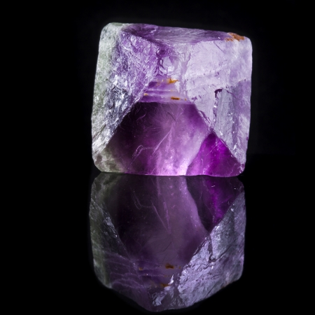 Beautuful Big Fluorite Crystal Purple with reflection on black surface background photo
