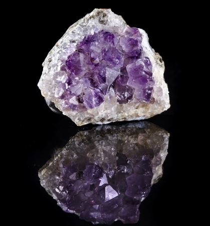 Natural cluster of Amethyst, violet variety of quartz close up macro with reflection on black surface background photo