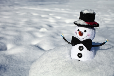 Happy Christmas snow man sitting in a snowy hill outdoors winter background photo