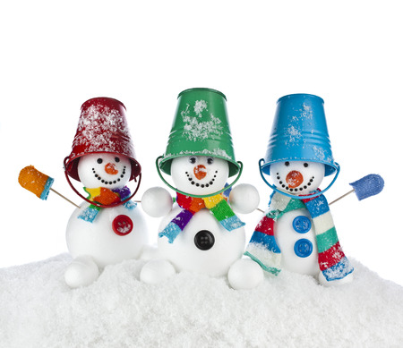 Three Cheerful snowmans in a striped scarfs, mittens and colorful bucket hat on his head isolated on white background photo