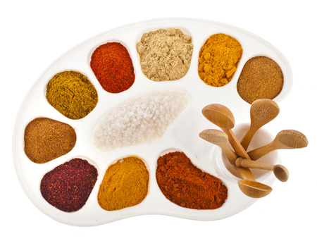 art palette for chief-cook with colorful powder spices and wooden spoon isolated on a white background photo