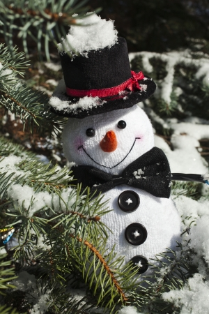 Happy Christmas snowman sitting in a snowy winter conifer fir tree photo