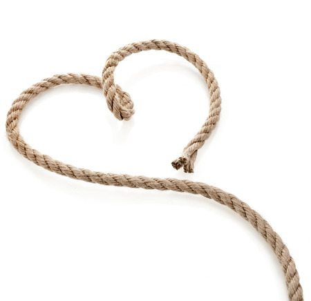 Heart Shaped Knoten auf einem Jute Seil auf weißem Hintergrund isoliert Lizenzfreie Bilder