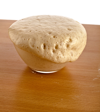 leavening: Rising Yeast Dough in glass bowl on wooden table Isolated on White Background