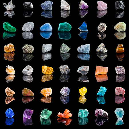 Collection set of semi-precious gemstones stones and minerals with reflection on black background photo