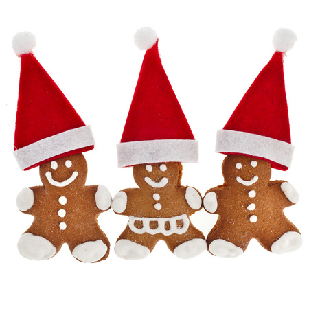 x mas: Three Gingerbread in santa red hat isolated on white background Stock Photo