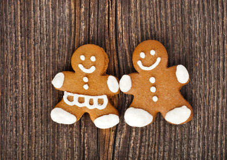 Fun Gingerbread couple on vintage wooden surface top view background photo