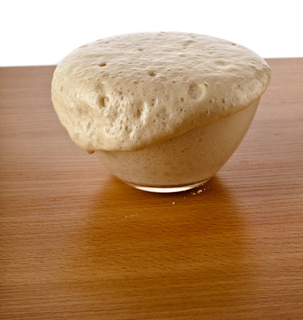 baker's: Rising Yeast Dough in bowl on wooden table Isolated on White Background Stock Photo