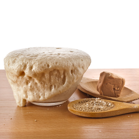 Rising Yeast Dough in bowl isolated on wooden table surface background photo