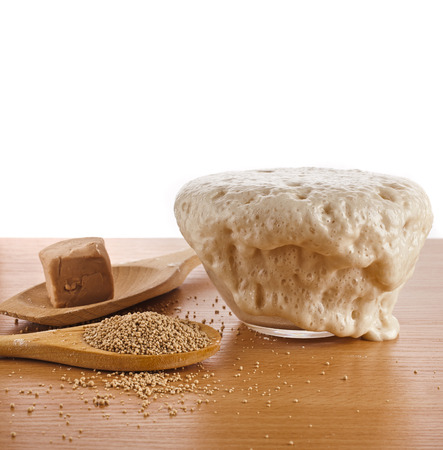 Rising Yeast Dough in bowl isolated on wooden table background photo