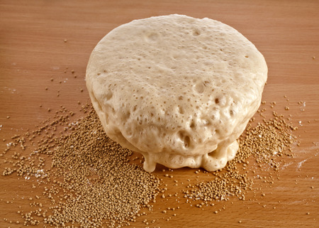 baker's: Rising Yeast Dough in bowl on wooden table background Stock Photo