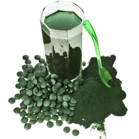 green powder: Spirulina algae powder glass drink nutritional supplement close up , isolated on white background