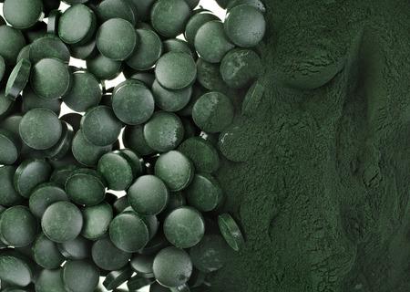 Spirulina-Pulver und Tabletten Algen Nahrungsergänzungsmittel Oberfläche Haufen Nahaufnahme Ansicht von oben, Hintergrund