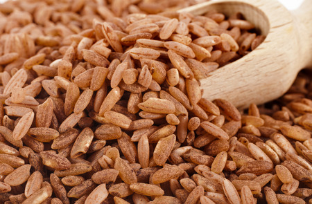 Brown Rice Heap in wooden scoop bowl Surface Close up Macro photo