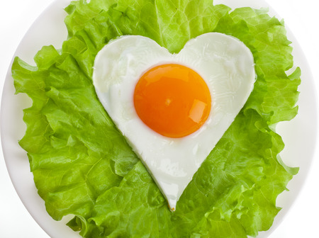 fried egg in shape of heart on a plate top view surface Isolated on white background photo