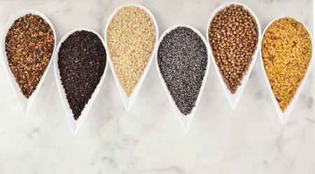 cebollin: diferentes semillas de especias en platos de porcelana blanca sobre fondo de mármol Foto de archivo