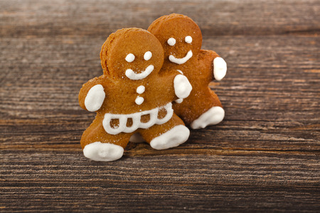 Gingerbread couple on the wooden surface, Christmas Holiday Background photo