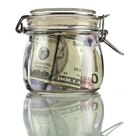 thrift box: Money glass jar full of savings isolated on white background