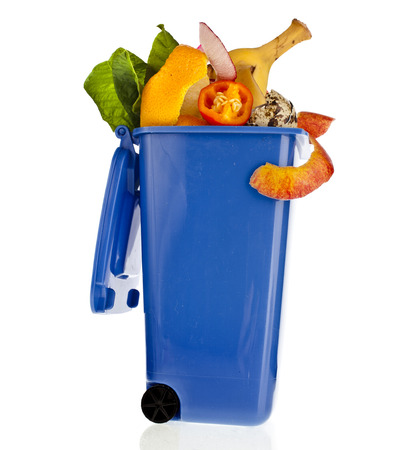 Blue garbage filled household waste kitchen scraps isolated on white background photo