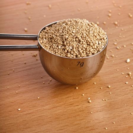 levadura: Montón de levadura seca en cuchara de metal en la mesa de la tabla de madera