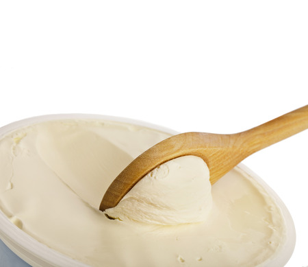 White cream on wooden spoon top view surface close up Isolated on White Background Stockfoto