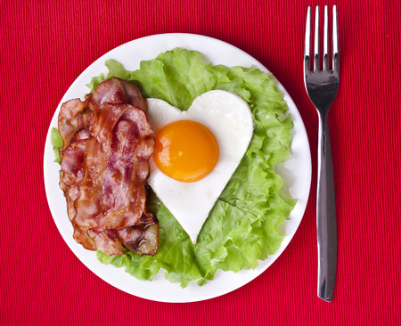 fried egg in shape of heart on a plate top view surface on red texture background photo