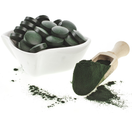 Spirulina algae powder and tablets in spoon , isolated on white background Standard-Bild