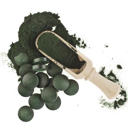 Spirulina Algen grünes Pulver und Tabletten in Löffel, isoliert auf weißem Hintergrund