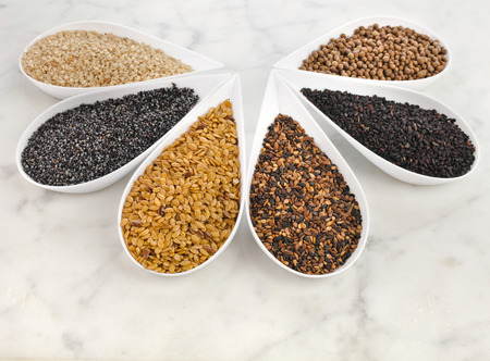 wholegrain mustard: different spice seed in white porcelain dishes over marble background
