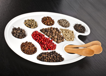palitra: Palitra with different colored peppercorn on black wooden board table background