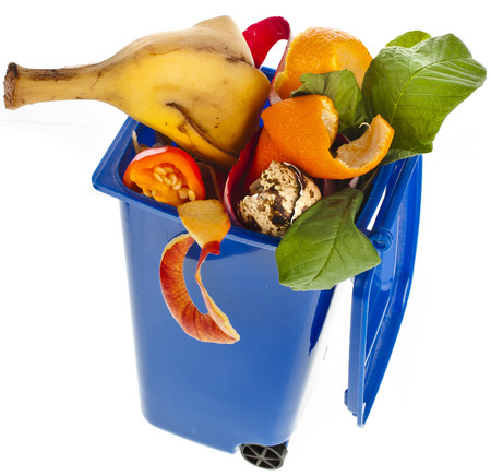 Blue Dumpster filled household waste kitchen scraps isolated on white background photo