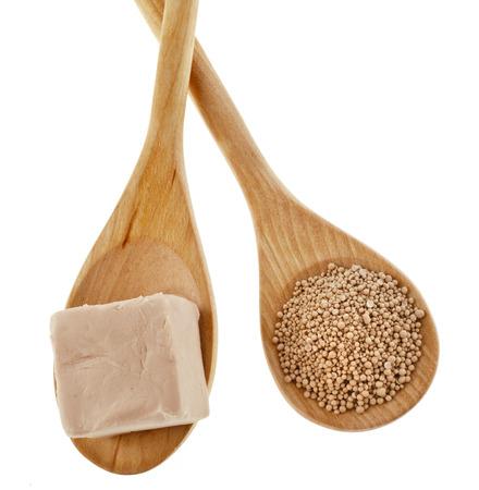 levadura: ingrediente de la hornada levadura en polvo en la cuchara de madera aislada en el fondo blanco