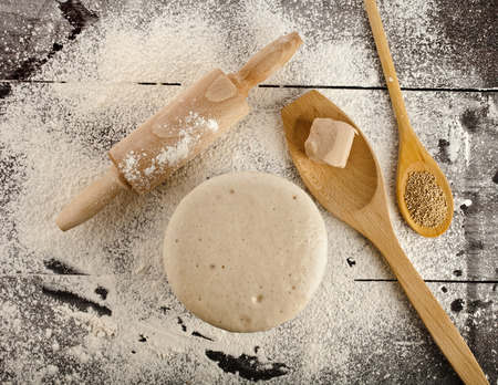 kitchen table top: Wooden rolling pin with white wheat flour on the black surface table   top view