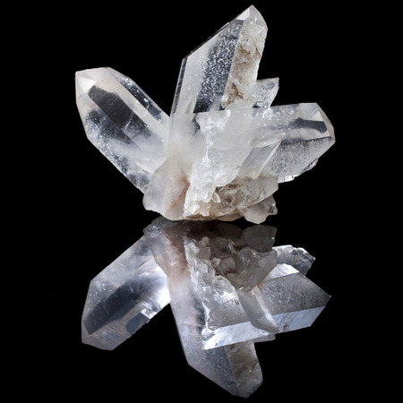 Lovely terminated white Quartz, Rock Crystal with reflection on black surface background photo