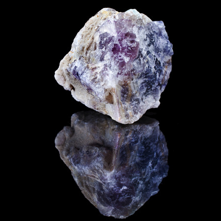 precious gem: Rough unpolished specimen of fluorite crystal with reflection on black surface background