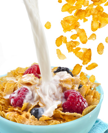 falling corn flakes with fresh berries and pouring milk isolated on white  photo