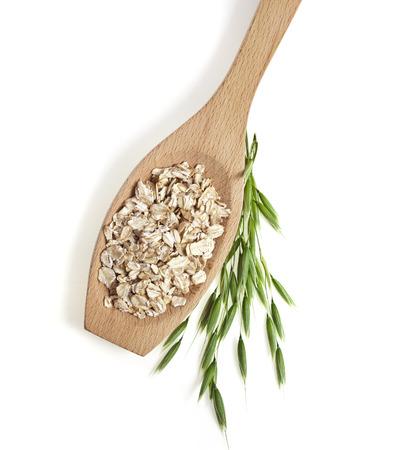 avena en hojuelas: semillas de avena de cerca en una cuchara de madera textura de la superficie aislada en el fondo blanco Foto de archivo