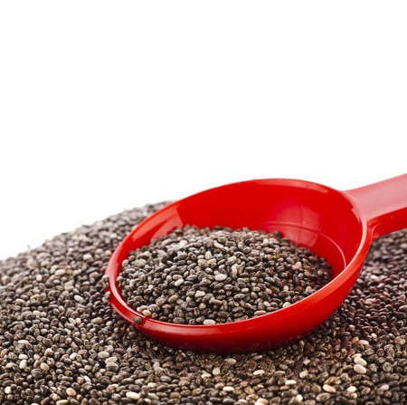 super macro: chia seeds in red scoop close up isolated on white Stock Photo