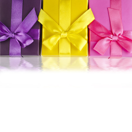 fancy box: colorful gift boxes wrapped ribbon bows surface close up isolated on white background