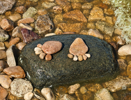 feet in sand: The footprint made up of stones on a stone island in the sea beach backdrop Stock Photo