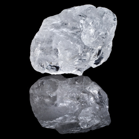 rough diamond: single white transparent Quartz, Rock Crystal with reflection on black surface background Stock Photo